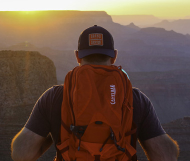 man wearing backwards baseball hat and red backpack staring off into the grand canyon