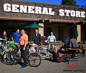 A group of people stand near bicycles in front of Tusayan General Store at the Grand Canyon