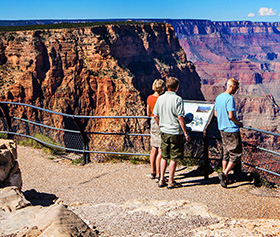 A family gazes out at the Grand Canyon